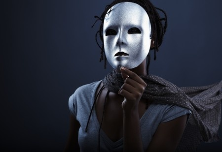 7874865 - gloomy woman in silver mask posing on a black background.